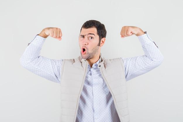 Junger mann in der beigen jacke, die muskeln zeigt und kraftvolle vorderansicht schaut.