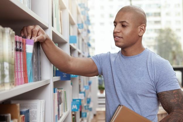 Junger mann in der bibliothek oder im buchladen
