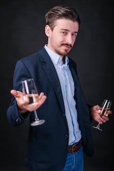 Junger mann in der blauen stellung mit champagnergläsern in den händen