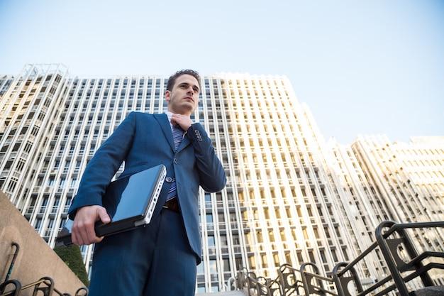 Junger mann in der eleganten klage, die mit dem laptop in seiner hand weg schaut aufwirft.