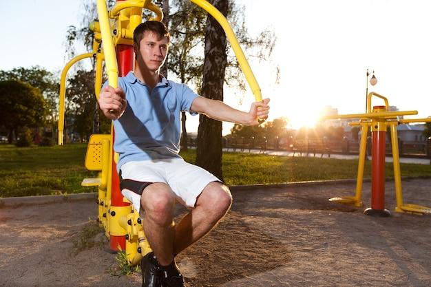 Junger mann in der freizeitkleidung, die auf der fitnessmaschine im freien sitzt und arbeitet