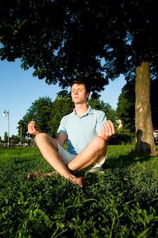 Junger mann in der freizeitkleidung, die auf grünem gras sitzt und im sonnenschein im park am klaren sommertag meditiert. konzept der inneren freiheit und des glücklichen lebensstils