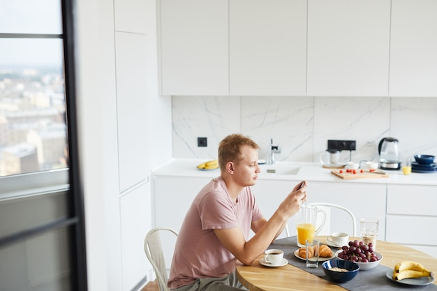Junger mann in der freizeitkleidung, die im smartphone durch bedienten tisch eine sms sendet