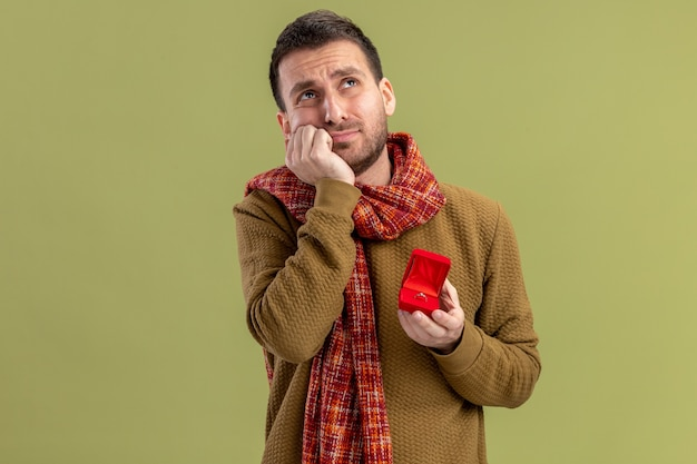 Junger mann in der freizeitkleidung mit schal um den hals, der rote box mit verlobungsring hält, der besorgten valentinstagkonzept über grüner wand steht