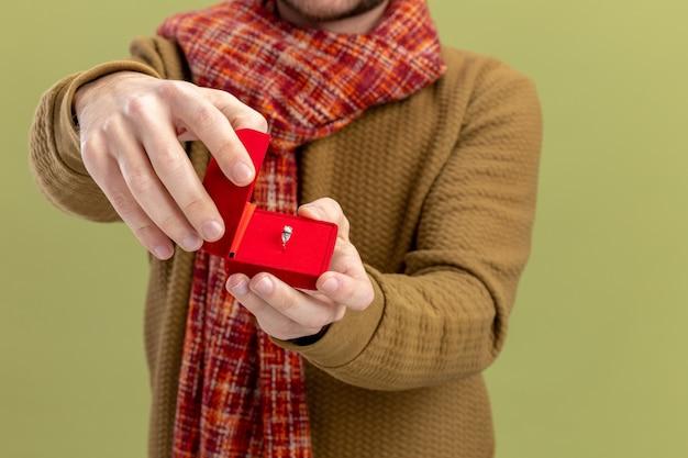 Junger mann in der freizeitkleidung mit schal um den hals, der rote box mit verlobungsring-valentinstagkonzept zeigt, das über grünem hintergrund steht