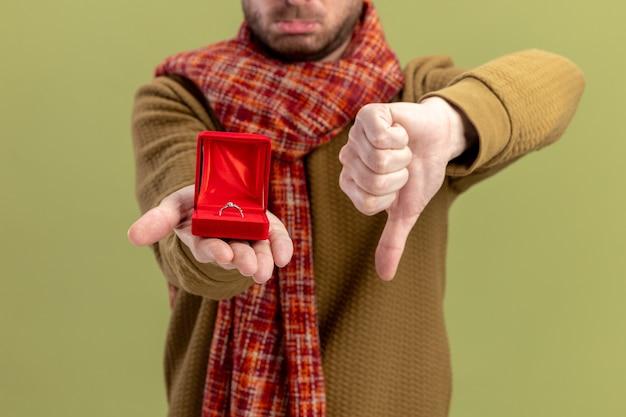 Junger mann in der freizeitkleidung mit schal um den hals, der rote box mit verlobungsring zeigt, der daumen unten valentinstagkonzept zeigt, das über grünem hintergrund steht