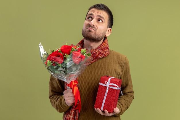 Junger mann in der freizeitkleidung mit schal um den hals, der strauß der roten rosen hält und geschenk, das oben mit dem traurigen ausdruck valentinstagkonzept steht, das über grüner wand steht