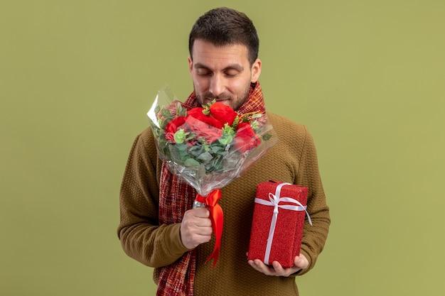 Junger mann in der freizeitkleidung mit schal um den hals, der strauß der roten rosen hält und glückliches und positiv lächelndes valentinstagkonzept darstellt, das über grünem hintergrund steht