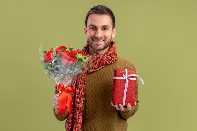 Junger mann in der freizeitkleidung mit schal um den hals, der strauß der roten rosen und der gegenwart hält, die das glückliche und fröhliche lächelnde valentinstagkonzept der kamera über grünem hintergrund betrachtet