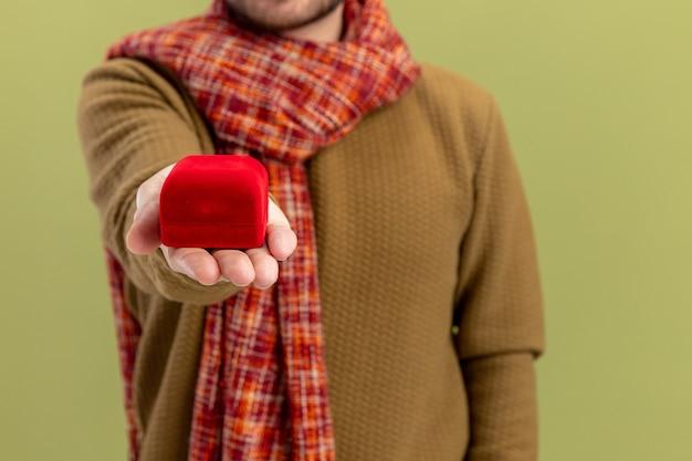 Junger mann in der freizeitkleidung mit schal um den hals zeigt rote box mit verlobungsring-valentinstagkonzept, das über grüner wand steht