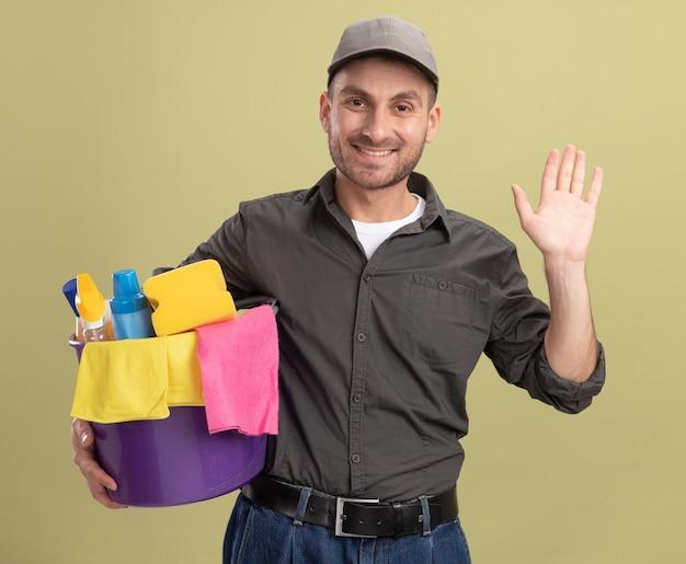Junger mann in der freizeitkleidung und in der kappe, die eimer mit den reinigungswerkzeugen hält, die fröhlich winkend mit der hand winkend über grüner wand winken