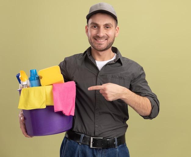 Junger mann in der freizeitkleidung und in der kappe, die eimer mit reinigungswerkzeugen hält, die mit zeigefinger auf ihn lächeln, zeigen zuversichtlich, über grüner wand stehend
