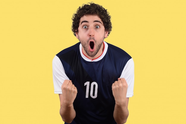 Junger mann in der fußballfußballuniform schreiend, während sein team gewinnt.