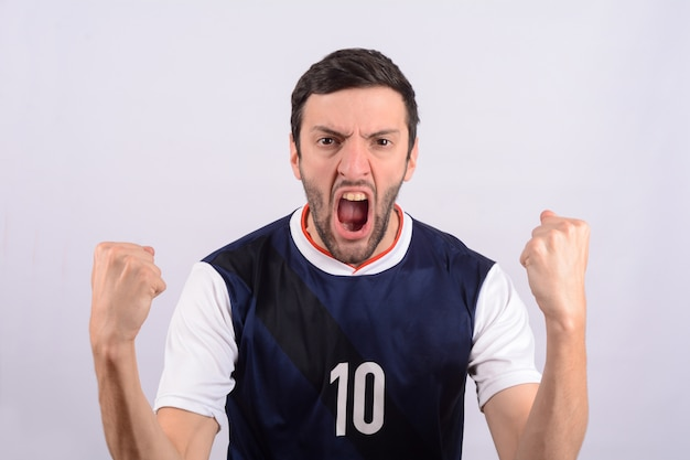 Junger mann in der fußballfußballuniform schreiend, während sein teamgewinn.