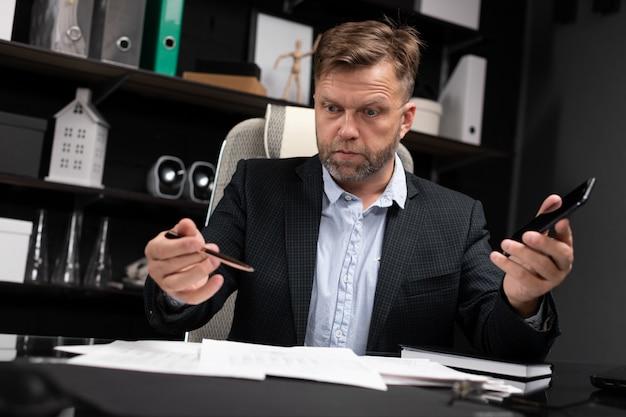 Junger mann in der geschäftskleidung, die am computertisch mit telefon und dokumenten arbeitet