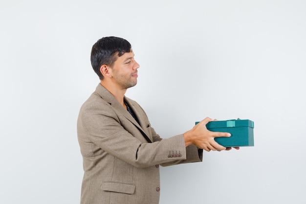Junger mann in der graubraunen jacke, die jemandem geschenk präsentiert und froh aussieht.