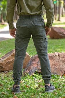Junger mann in der grünen hose, die im park steht