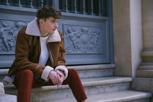 Junger mann in der jacke, die an der haustür sitzt
