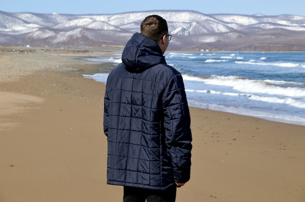 Junger mann in der jacke, die auf dem strand des japanischen meeres geht