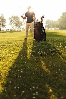 Junger mann in der kappe, die golfschläger hält