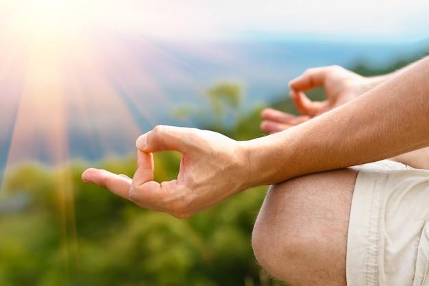 Junger mann in der lotoshaltung. übendes yoga des mannes draußen