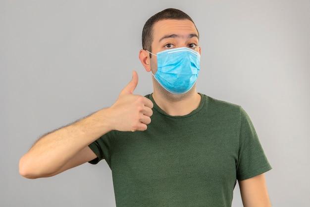 Junger mann in der medizinischen maske, die ok zeichen tut, daumen hoch mit fingern lokalisiert auf weiß