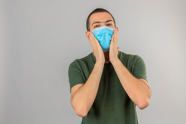 Junger mann in der medizinischen maske, die seine wangen berührt, lokalisiert auf weiß