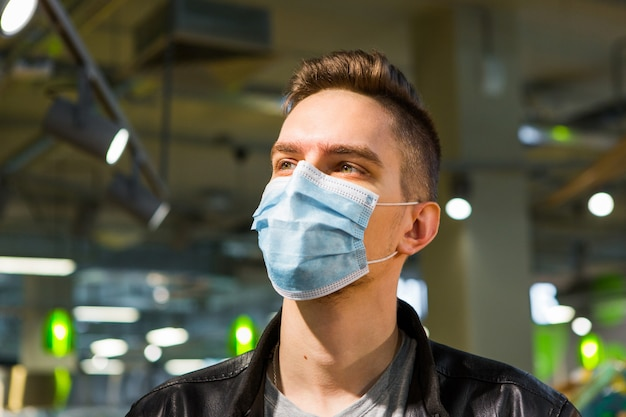 Junger mann in der medizinischen maske. quarantänesicherheit. mann im laden