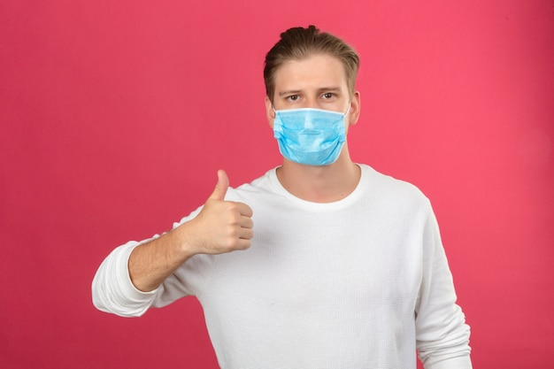 Junger mann in der medizinischen schutzmaske, die kamera betrachtet, die daumen oben steht, die über lokalisiertem rosa hintergrund stehen