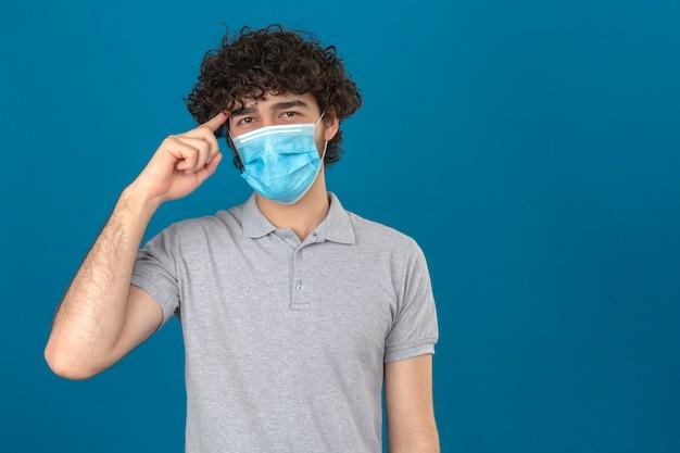 Junger mann in der medizinischen schutzmaske, die tempel mit fingerdenken zeigt, konzentrierte sich auf eine aufgabe über lokalisiertem blauem hintergrund