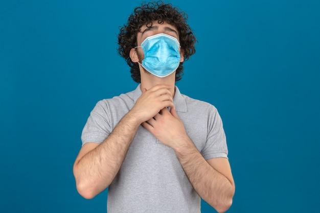 Junger mann in der medizinischen schutzmaske hält hände an seinem hals wegen halsschmerzen über isoliertem blauem hintergrund