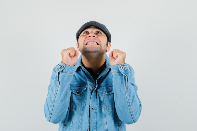 Junger mann in der mütze, im t-shirt, in der jacke, die siegergeste zeigt und glücklich schaut