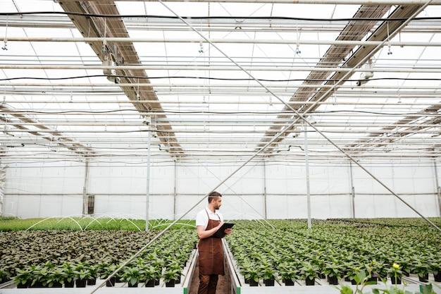 Junger mann in der schürze, die mit pflanzen im grün arbeitet
