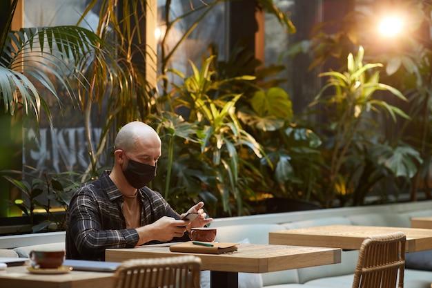 Junger mann in der schutzmaske unter verwendung des mobiltelefons beim sitzen am tisch im café