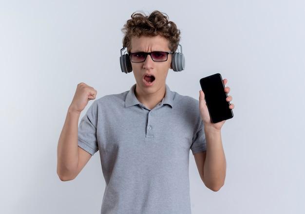 Junger mann in der schwarzen brille, die graues polohemd mit kopfhörern trägt, die das glückliche und aufgeregte stehen der geballten faust des smartphones über weißer wand zeigen