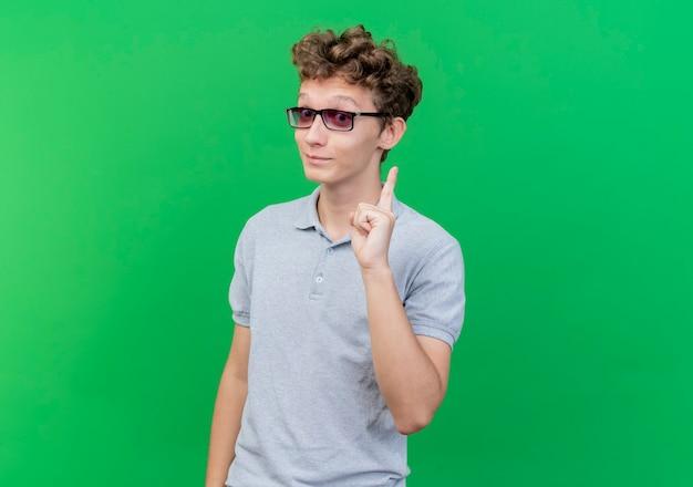 Junger mann in der schwarzen brille, die graues poloshirt glücklich und positiv zeigt zeigefinger, der neue idee über grün zeigt