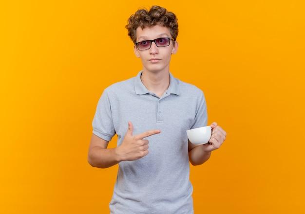 Junger mann in der schwarzen brille, die graues poloshirt hält, das kaffeetasse hält, die mit dem finger darauf zeigt und mit ernstem gesicht über grün beiseite schaut