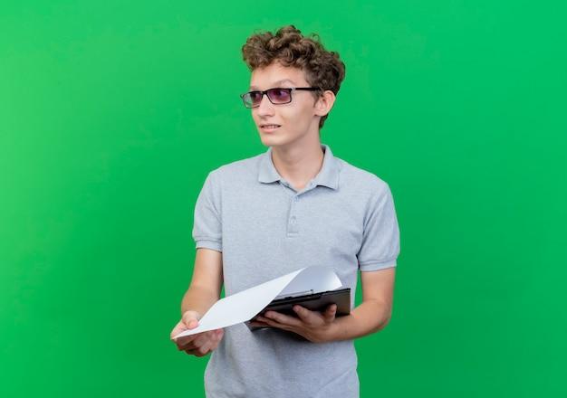 Junger mann in der schwarzen brille, die graues poloshirt hält, das klemmbrett hält, das mit skeptischem ausdruck über grün beiseite schaut