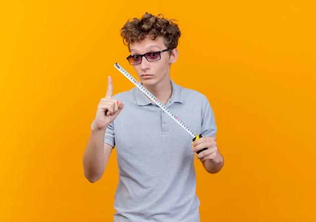 Junger mann in der schwarzen brille, die graues poloshirt hält, das maßband lächelnd glücklich und positiv zeigt zeigefinger mit neuer idee über orange