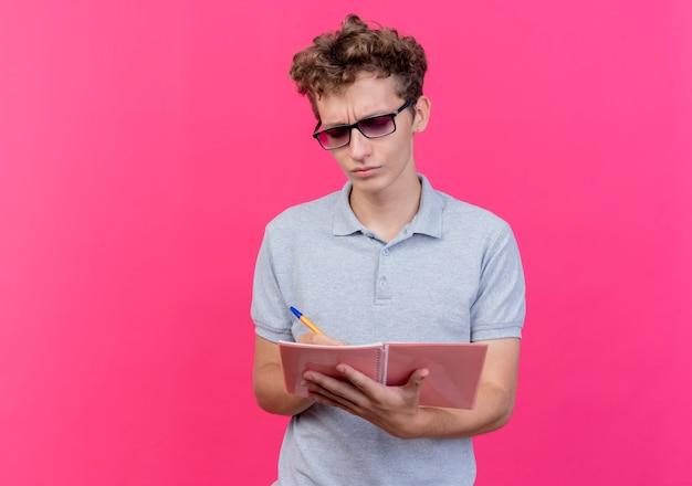Junger mann in der schwarzen brille, die graues poloshirt hält, das notizbuch mit stift hält, der es mit ernstem stirnrunzeln gesicht über rosa betrachtet