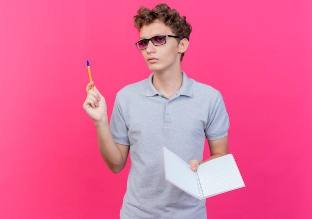 Junger mann in der schwarzen brille, die graues poloshirt hält, das notizbuch mit stift mit ernstem gesicht hält, das über rosa wand steht