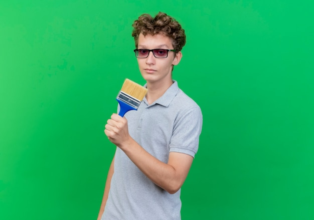 Junger mann in der schwarzen brille, die graues poloshirt hält, das pinsel hält, das an der kamera mit ernstem skeptischem gesicht über grün lokalisiert