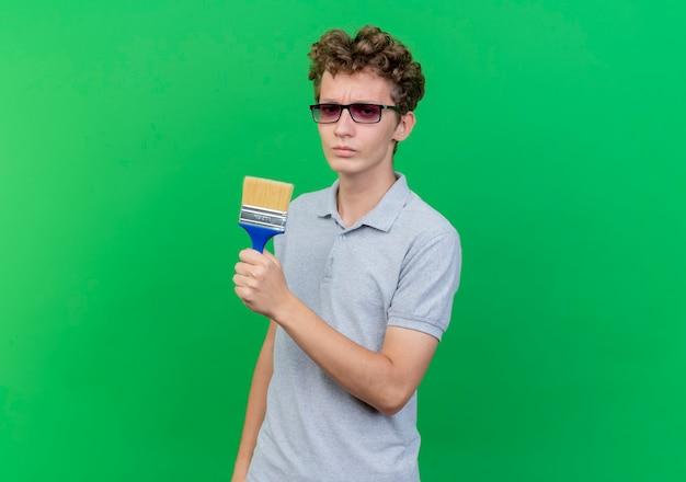 Junger mann in der schwarzen brille, die graues poloshirt hält, das pinsel hält, das an kamera mit ernstem gesicht über grün lokalisiert