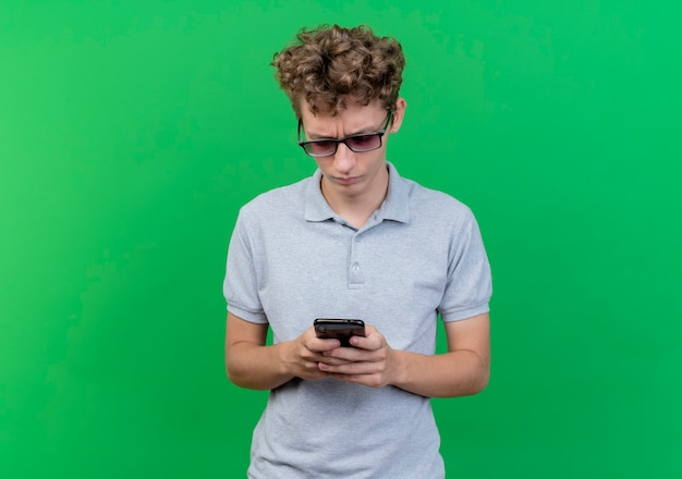 Junger mann in der schwarzen brille, die graues poloshirt hält, das smartphone betrachtet, das es mit ernstem gesicht über grün betrachtet