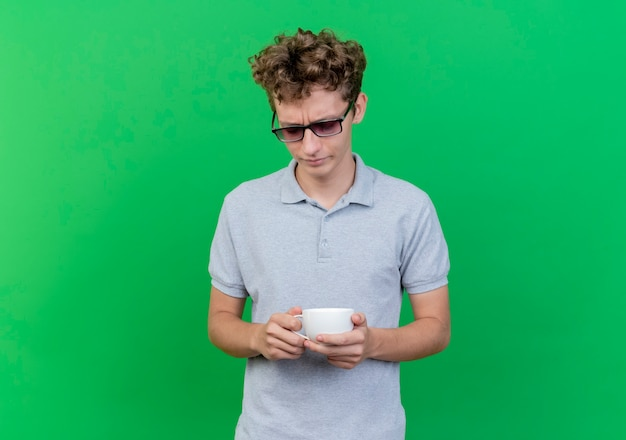 Junger mann in der schwarzen brille, die graues poloshirt hält kaffeetasse, die unten mit traurigem ausdruck steht, der über grüner wand steht