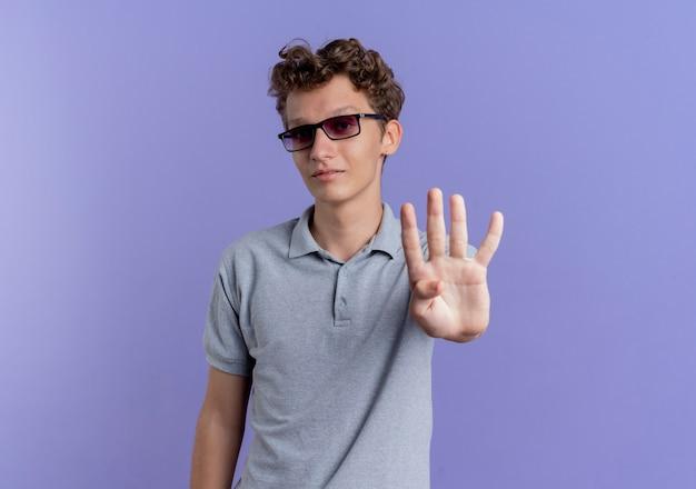 Junger mann in der schwarzen brille, die graues poloshirt mit lächeln auf gesicht zeigt und mit fingern nummer vier zeigt, die über blauer wand stehen