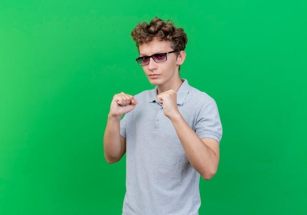 Junger mann in der schwarzen brille, die graues poloshirt mit selbstbewusstem ausdruck mit geballten fäusten trägt, die wie boxer über grün aufwerfen