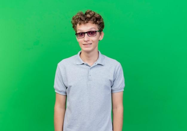 Junger mann in der schwarzen brille, die graues poloshirt mit skeptischem lächeln trägt, das über grüner wand steht