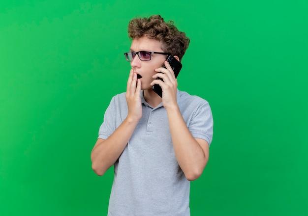 Junger mann in der schwarzen brille, die graues poloshirt trägt, das auf handy spricht, das über grün erstaunt und überrascht wird