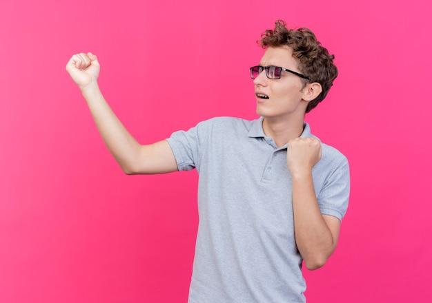 Junger mann in der schwarzen brille, die graues poloshirt trägt, das die fäuste glücklich und aufgeregt über rosa ballt